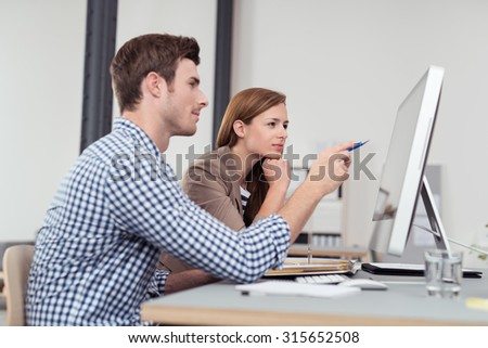 Two Young Businesspeople Sitting at the Table and Looking at the Figures on the Computer Screen - stock photo