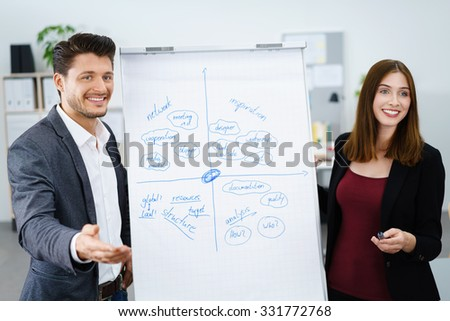 two young businesspeople standing beside the whiteboard - stock photo