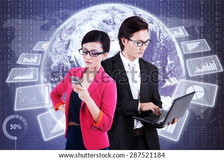 Two young businesspeople working together in front of futuristic interface with virtual financial statistics