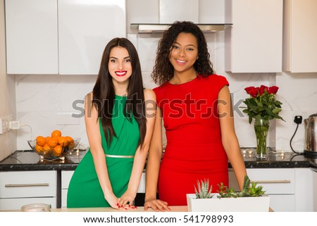 Two young businesswoman standing on the kitchen.