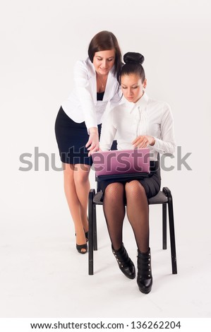 Two young businesswoman with laptop at white background - stock photo