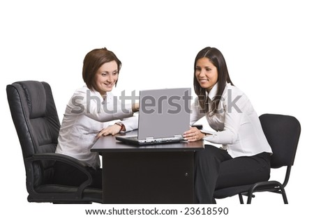 Two young businesswoman working together on a laptop at their office desk.