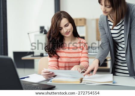 Two young businesswomen checking a document at a desk in the office that they have just removed from a large binder - stock photo
