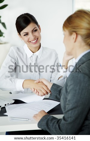 two young businesswomen shaking hands - stock photo