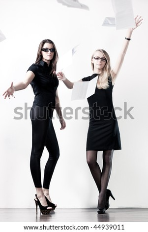 Two young businesswomen throwing out paper. On bright white wall background. - stock photo