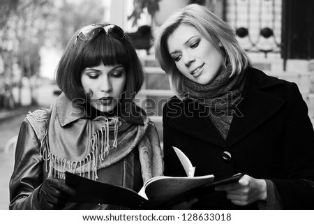 Two young businesswomen with a folder - stock photo