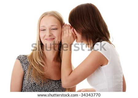 Two young casual caucasian woman gossiping isolated against white background - stock photo