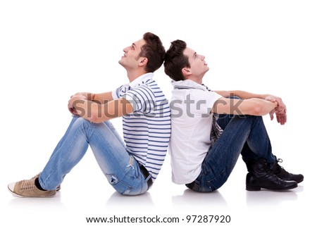 two young casual men sitting back to back on white background and looking at something on both sides of the picture