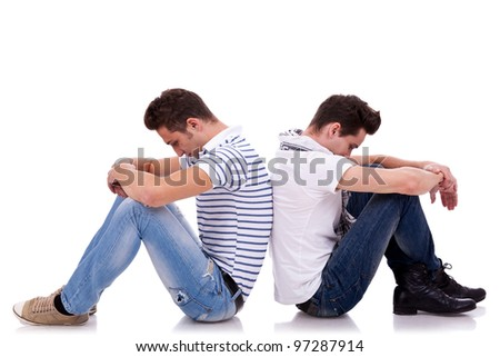 two young casual men sitting back to back on white background and looking very sad