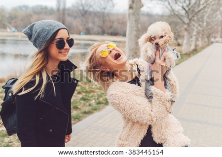 two young caucasian cute girls portrait with dog outdoor in park walking happy and smile all the way  - stock photo