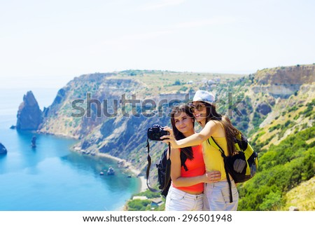 two young caucasian females making self portrait on a cliff above the sea - stock photo