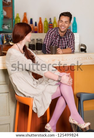 two young caucasian people sitting at the counter in a colorful cafe socializing and having fun - stock photo