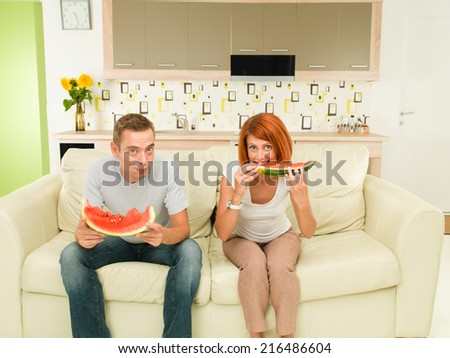 two young caucasian people sitting on sofa, eating watermelon - stock photo