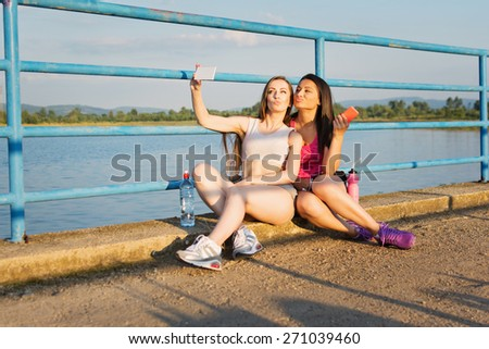 Two young Caucasian women taking a selfie relaxing after running. Two gorgeous fitness girl sitting by the lake wearing sportswear taking a self portrait. Natural light, mild retouch. - stock photo