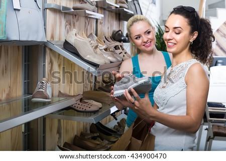 Two young cheerful girls choosing shoes together in the fashion store. Selective focus - stock photo