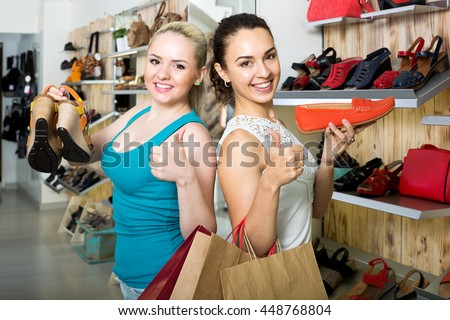 Two young cheerful girls shopping together in the fashion store - stock photo