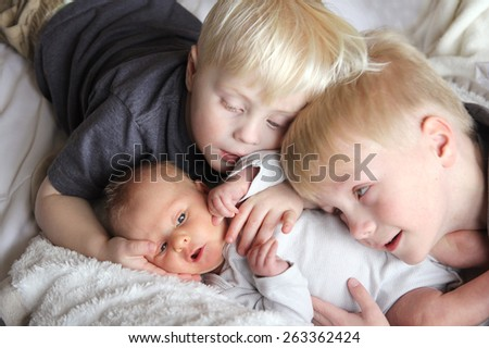 Two young children, a toddler and his big brother are lovingly hugging their newborn baby sister. - stock photo