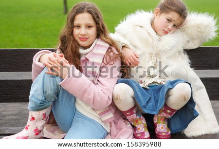 Two young children and family sisters sitting together in a park wooden bench with green grass, having an argument and fighting during a cold winter day outdoors. - stock photo