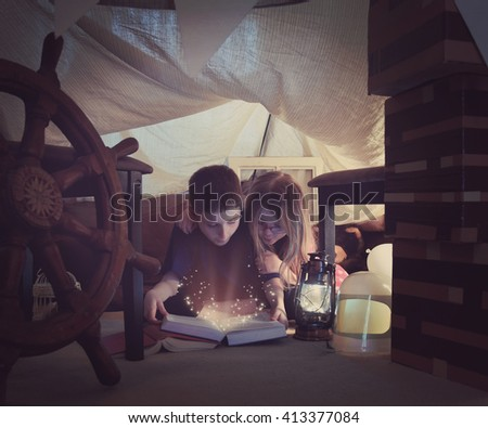 Two young children are reading a book together with sparkles in a tent fort at home for a story time or learning concept. - stock photo