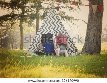 Two young children are reading books together outside in a tepee tent for a education or learning concept. - stock photo