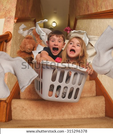 Two young children are riding in a laundry basket down the house stairs with socks flying for a parenting, babysitter or humor concept. - stock photo