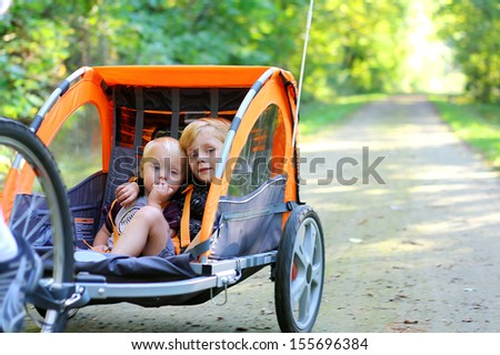 Two young children are sitting together in a pull behind bicycle trailer as they ride down a bike trail in the woods - stock photo