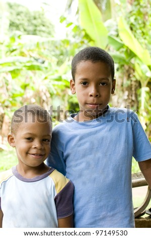 two young children brothers smiling portrait with jungle tropical plants in background Big Corn Island Nicaragua Central America - stock photo