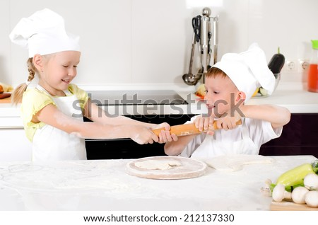 Two young children dressed in white chefs aprons and toques fighting over a rolling pin in the kitchen as they both want to roll out their dough for homemade pizza - stock photo