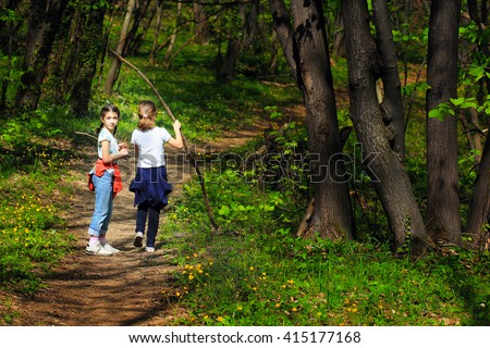 Two young children, girls walking through the woods along a path through the woods
