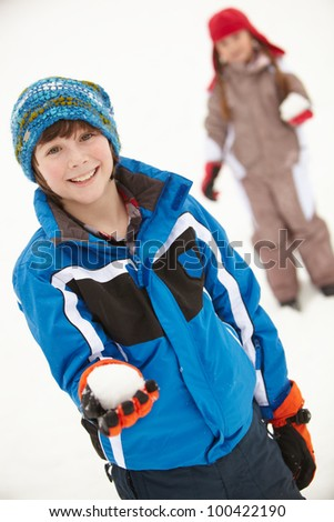 Two Young Children Having Snowball Fight Wearing Woolly Hats - stock photo
