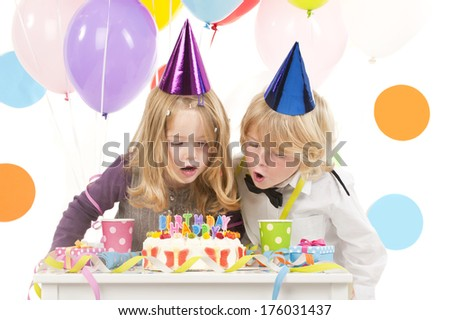 Two young children in party hats with a birthday cake.