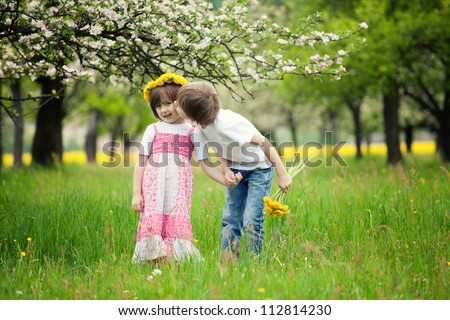 Two young children kissing in flowery meadow of long grass, girl wearing daisy flower crown. - stock photo