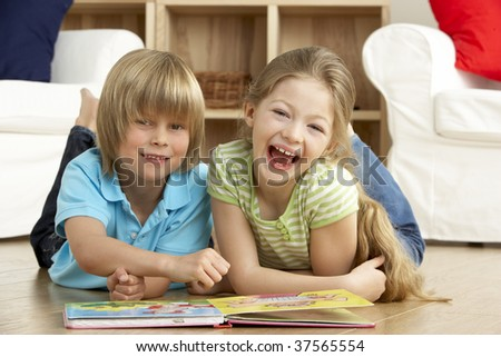 Two Young Children Reading Book at Home - stock photo