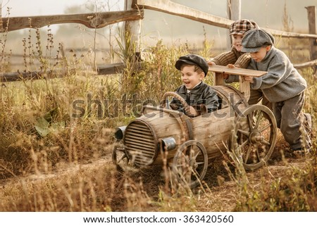 Two young children ride in the third race car from wooden barrels on a rural road autumn evening - stock photo