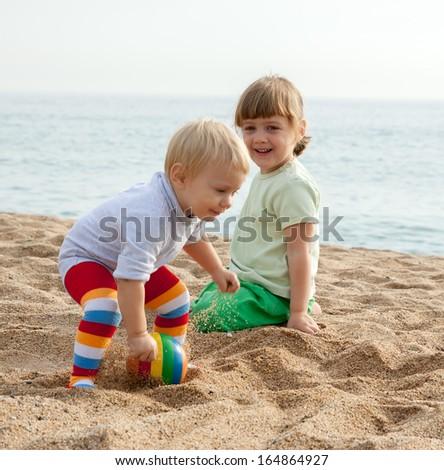 Two young children sitting on beach