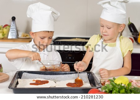 Two young children wearing chefs uniforms making themselves a homemade pizza spreading the tomato paste onto the pastry for the base on a baking tray