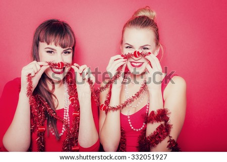 Two young christmas women on a red background