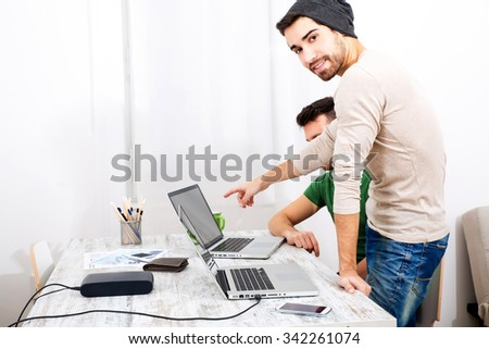 Two young colleagues discussing something in the office - stock photo