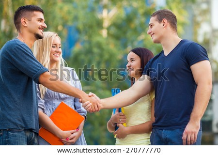 Two young couple meeting on the street - stock photo