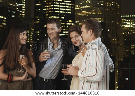 Two young couples drinking together against city skyline at night - stock photo