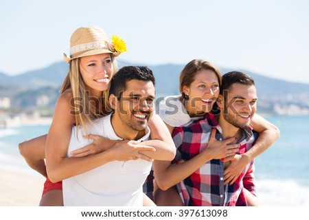 Two young couples  having fun on sand beach at summer day