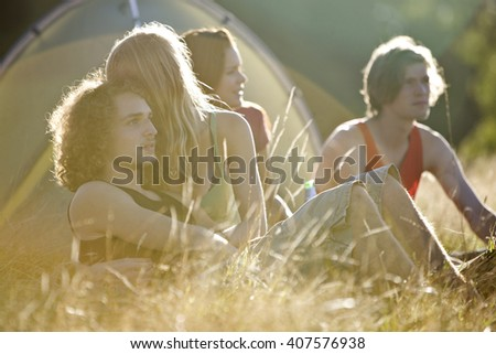 Two young couples sitting in front of a tent - stock photo