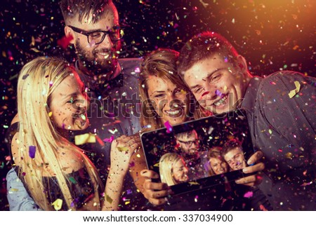 Two young couples taking a selfie at midnight on a New Year's Eve party - stock photo
