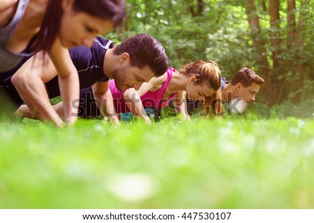 Two young couples working out doing push-ups outdoors in a park with an extreme low angle view across the top of the grass of their heads and shoulders