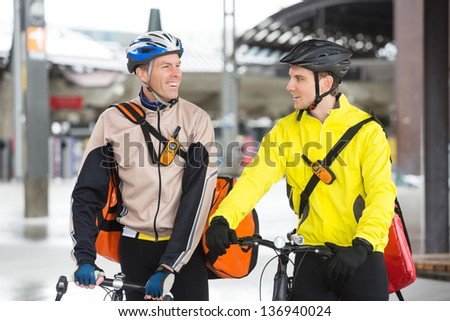Two young courier delivery men in protective gear with bicycles looking at each other - stock photo