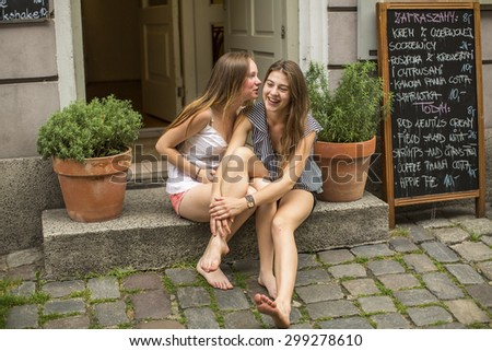Two young cute girls girlfriend sitting on the steps of the cafe and whispering. - stock photo