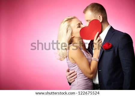 Two young dates kissing behind paper heart