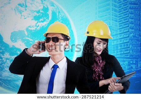 Two young engineer using cellphone and tablet to communicate, shot with world map in futuristic interface - stock photo