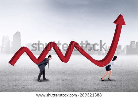 Two young entrepreneurs work together to carry a business graph with upward arrow - stock photo