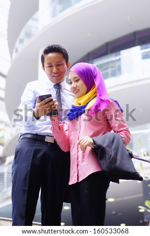 Two young executive looking at tablet phone outdoor